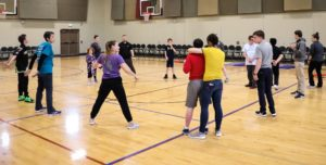 A group of people in a loose circle in a gym, playing a game together